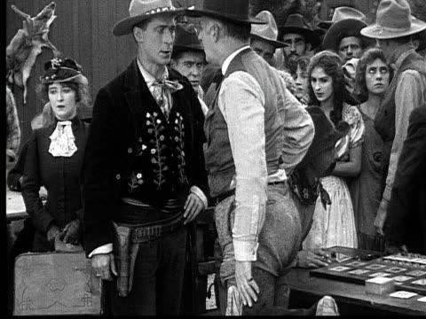 vídeos de stock, filmes e b-roll de 1915 b/w medium shot cowboy telling gambler to leave gambling saloon while crowd watches  - faroeste