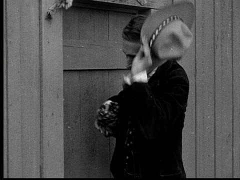 1915 b/w medium shot cowboy wiping his face with handkerchief outside door  - sweat stock videos & royalty-free footage