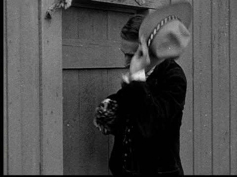 1915 B/W Medium shot Cowboy wiping his face with handkerchief outside door