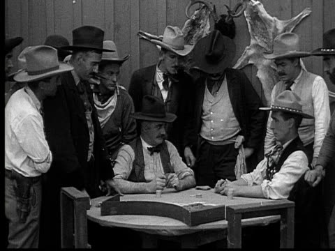 1915 B/W Medium shot Cowboys playing poker in gambling saloon