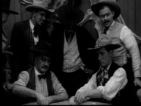 1915 B/W Medium shot Cowboys playing poker in gambling saloon
