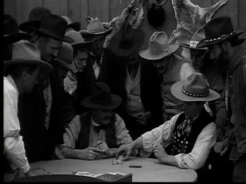 1915 b/w medium shot cowboys playing poker in gambling saloon  - 1915年点の映像素材/bロール