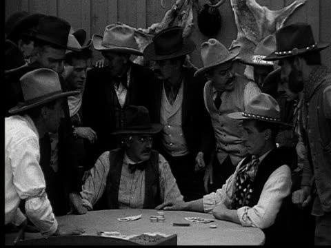 1915 b/w medium shot cowboys playing poker in gambling saloon  - poker card game stock videos & royalty-free footage