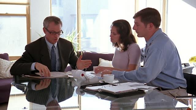 medium shot crane shot financial advisor talking to couple - financial advisor stock videos & royalty-free footage