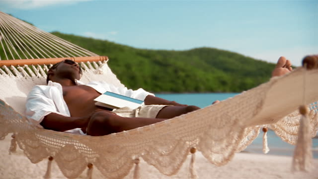 medium shot crane shot man sleeping in swinging hammock on beach with book resting on stomach - hammock stock videos & royalty-free footage