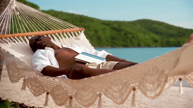 medium shot crane shot man sleeping in swinging hammock on beach with book resting on stomach - crane shot stock videos & royalty-free footage