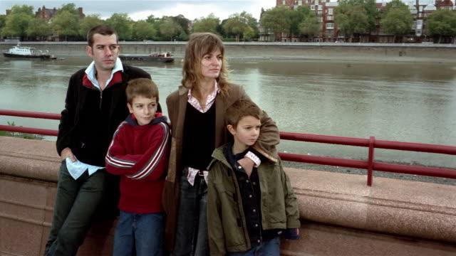 Medium shot crane shot parents and two sons leaning against railing at riverfront / Battersea Park, London