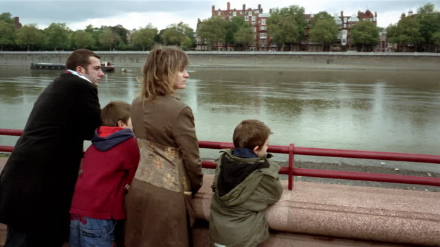 medium shot crane shot parents and two sons leaning looking out over water at riverfront / battersea park, london - battersea stock videos & royalty-free footage