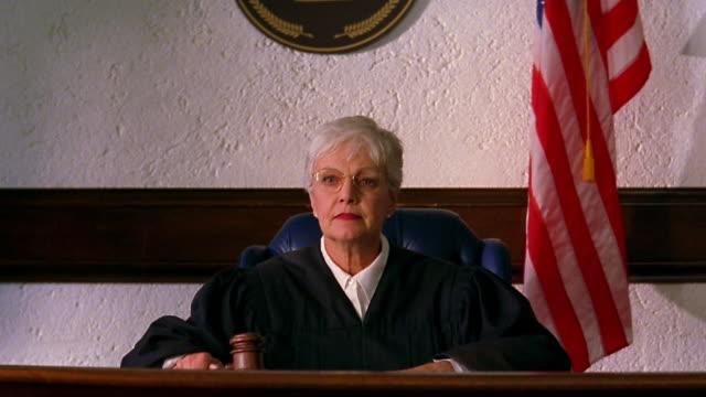 medium shot crane shot senior female judge sitting at bench / pounding gavel / american flag in background - giudice video stock e b–roll