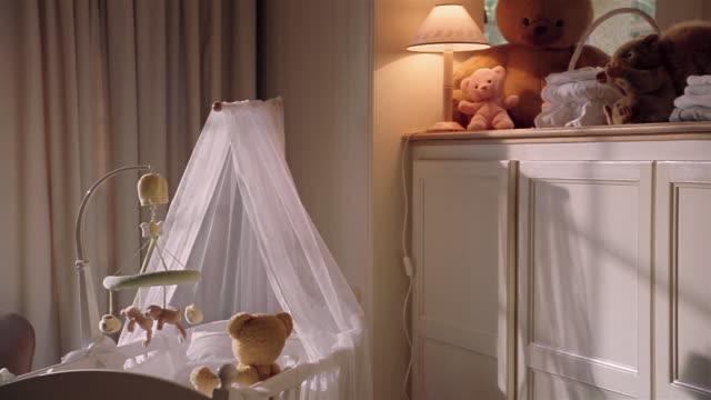 medium shot crib and teddy bears on shelf over cabinets in nursery - cot stock videos & royalty-free footage
