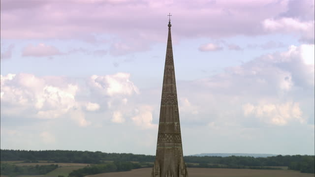 Medium shot cross and steeple/ zoom out aerial Salisbury Cathedral/ Salisbury, England