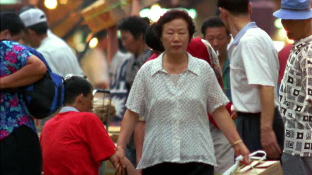 Medium shot crowd moving through outdoor market