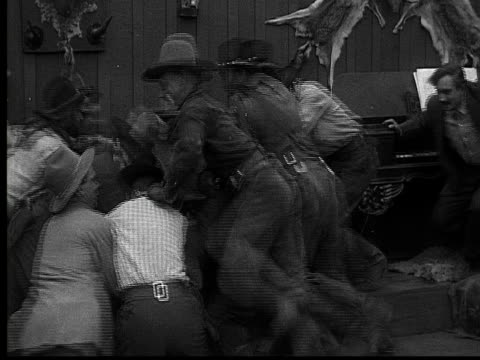 vidéos et rushes de 1915 b/w medium shot crowd of cowboys diving into a pile on floor of saloon  - ouest américain