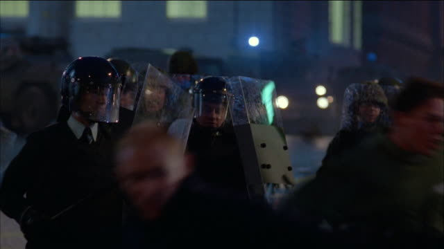 medium shot crowd running from riot police / soldiers lining up behind shields - anger stock videos & royalty-free footage
