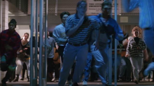 medium shot crowd rushing out of stadium at night - terrified stock videos & royalty-free footage