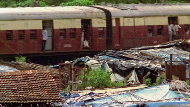 Medium shot crowded passenger train passing shacks / Bombay