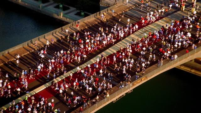 hs medium shot crowds of marathon runners / tilt up zoom out to chicago skyline - marathon stock videos & royalty-free footage