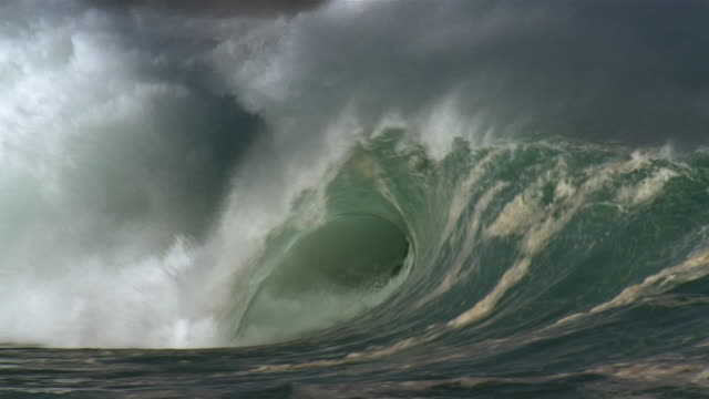 medium shot curl of waves breaking in waimea bay / oahu, hawaii - curled up stock videos and b-roll footage