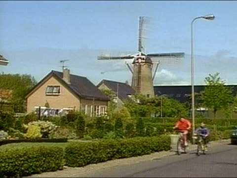 1994 medium shot cyclists riding past windmill followed by car with dog in window / Holland / AUDIO