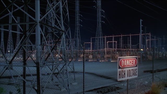 vídeos y material grabado en eventos de stock de medium shot danger sign lit up on fence of electrical power plant at night / crane shot electric towers / california - electricidad