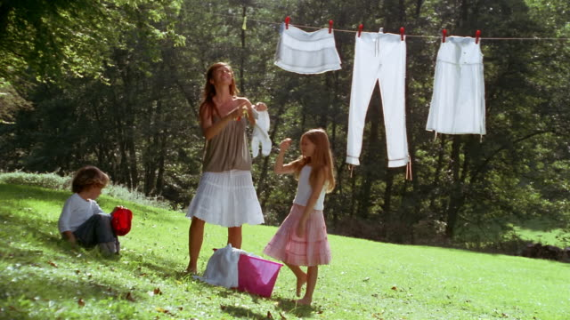 Medium shot daughter helping mother hang laundry on clothesline / young boy holding pail and pulling up grass