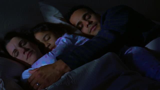 Medium shot daughter sleeping in bed with her parents