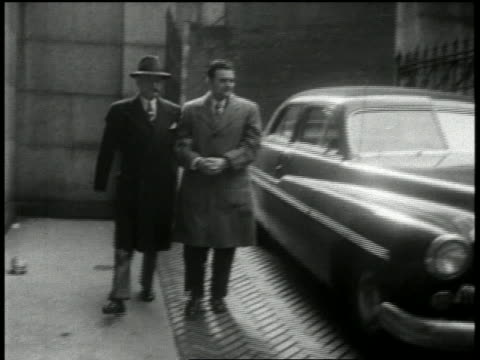 1951 medium shot david greenglass in cuffs being escorted by two men / nyc - 1951 stock videos & royalty-free footage