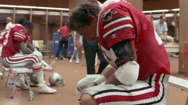 1985 medium shot dejected tampa bay bandits football player doug beaudoin sitting on bench in locker room / tampa, florida, usa  - loss stock videos & royalty-free footage