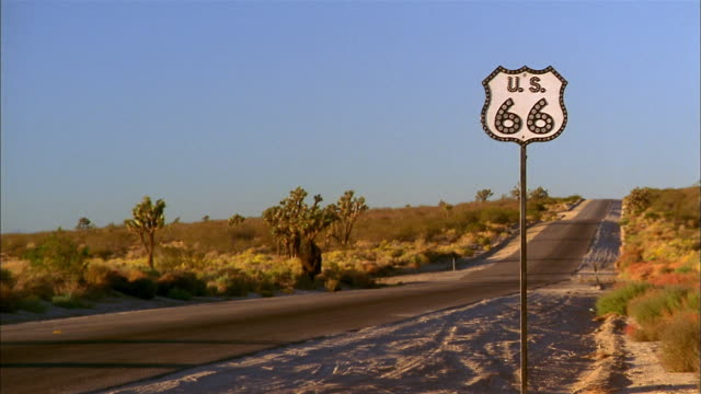 Medium shot deserted highway in desert plains w/Route 66 highway sign in foreground