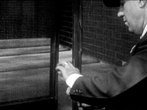 1947 medium shot detective dusting window frame for fingerprints/ dearborn, michigan - only mature men stock videos & royalty-free footage