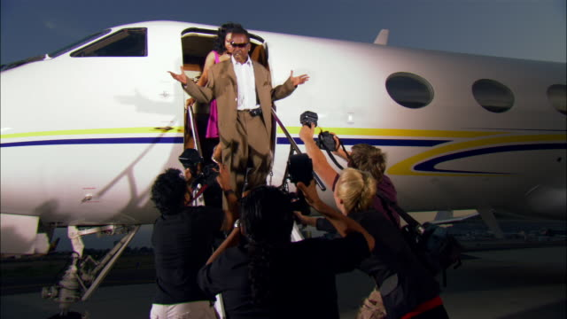 vidéos et rushes de medium shot diva and businessman exiting private airplane, posing for paparazzi photographers and walking away / long beach, california, usa - fierté