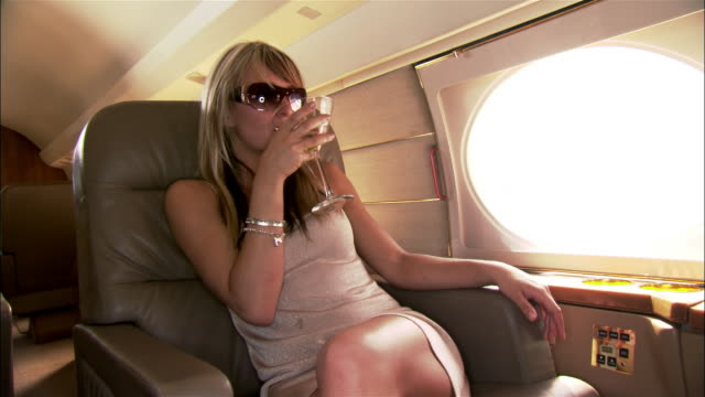 medium shot diva drinking martini and laughing on private airplane - private jet stock videos & royalty-free footage