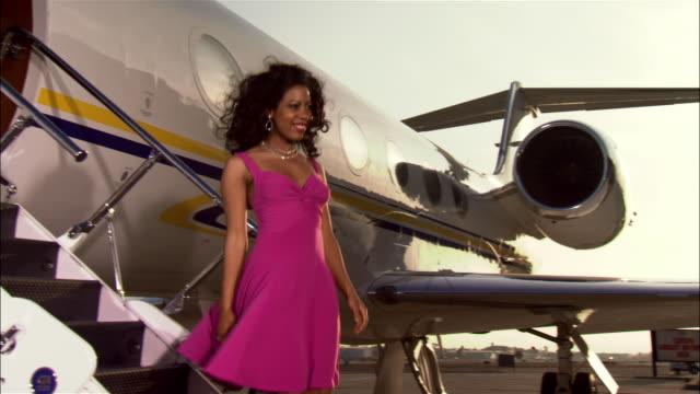 Medium shot Diva waving and exiting private airplane, then turns and walks away / Long Beach, California, USA