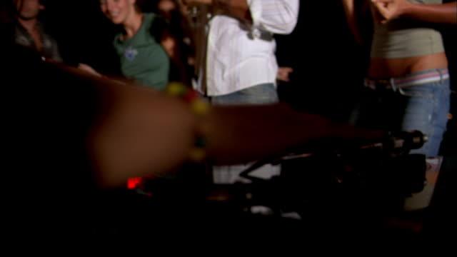 medium shot dj playing music w/people dancing in background - dj stock videos & royalty-free footage