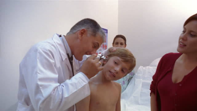 medium shot doctor checking boy's ears while his mother and nurse watch in office/ panama city, panama  - boy medical exam stock videos and b-roll footage