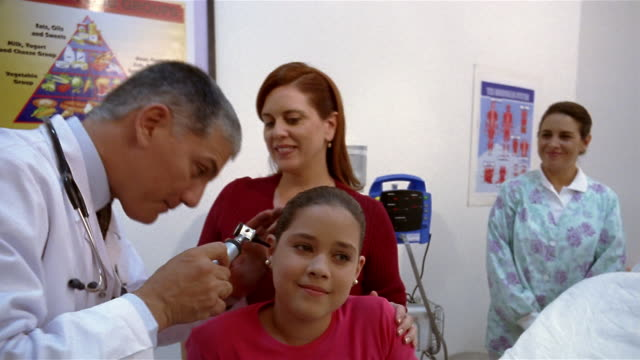 medium shot doctor checking girl's ears and eyes while her mother and nurse watch in office/ panama city, panama  - optometrist stock videos & royalty-free footage