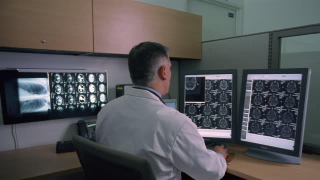 Medium shot Doctor examining brain scan on computer monitors/ Panama City, Panama