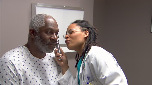 Medium shot doctor examining patient's ear with otoscope