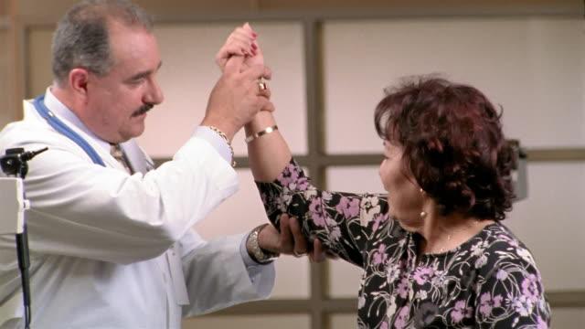 vidéos et rushes de medium shot doctor examining senior woman's arm / el paso, texas - cabinet médical