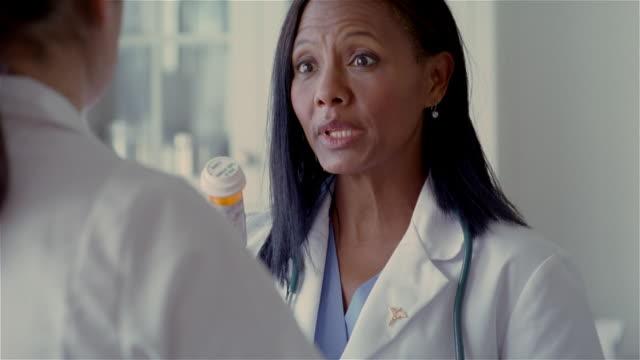 medium shot doctor explaining prescription to nurse/ solebury, pennsylvania - caduceus stock videos & royalty-free footage