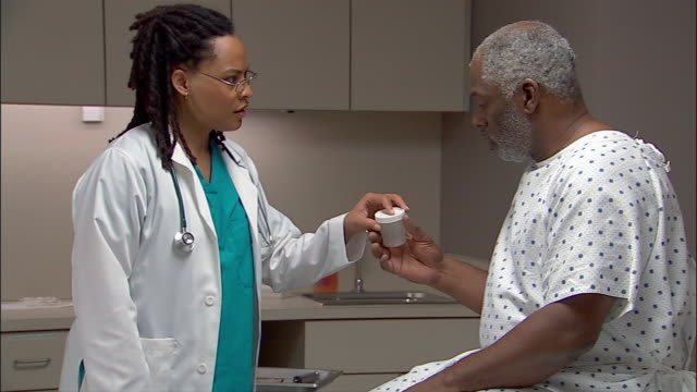 Medium shot doctor handing man in hospital gown a specimen cup