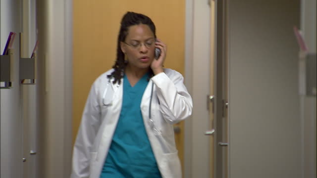 Medium shot doctor talking on cell phone in hallway / retrieving patient chart and entering examination room
