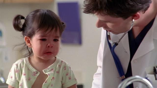 Medium shot doctor wiping crying toddler's tears during exam / El Paso, Texas