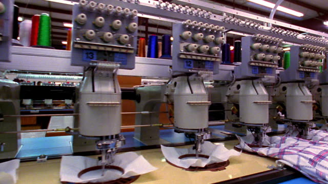 medium shot dolly shot along automated sewing machines in textile factory / el paso, texas - macchina per cucire video stock e b–roll