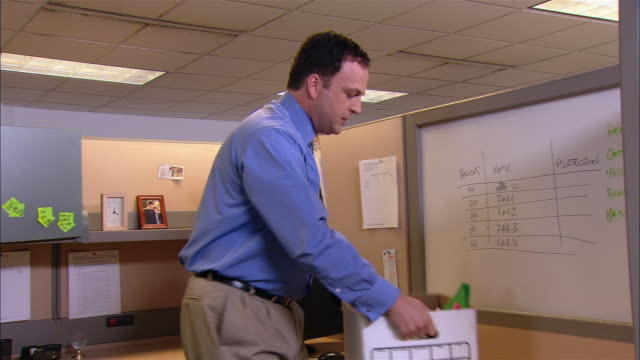 Medium shot dolly shot angry man carrying belongings in cardboard box after being terminated / walking past co-workers in cubicles