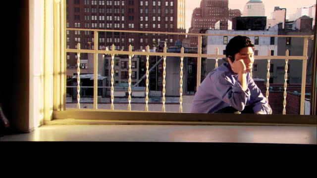 medium shot dolly shot asian man sitting on balcony and talking on cellular phone / nyc - balcony stock videos & royalty-free footage