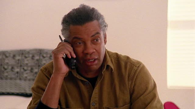 medium shot dolly shot black man talking on phone - sladdlös telefon bildbanksvideor och videomaterial från bakom kulisserna