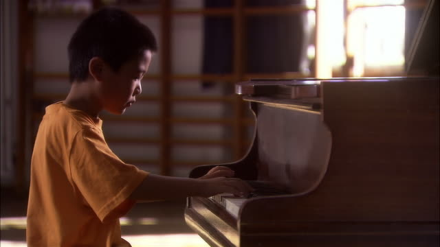medium shot dolly shot boy playing piano in schoolroom - ピアノ点の映像素材/bロール