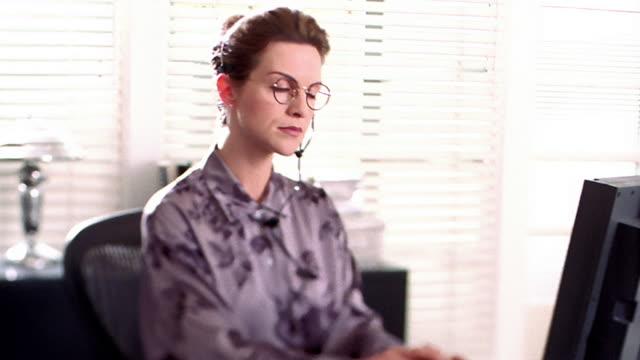 vídeos de stock, filmes e b-roll de medium shot dolly shot businesswoman talking on headset, working on computer and smiling at camera - alto contraste