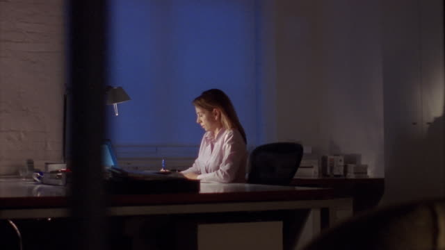 Medium shot dolly shot businesswoman working on computer in office at night